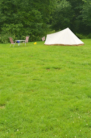 Campsite with a canvas tent mounted on grass - space for text photo