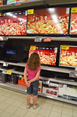 carrefour market: Television store - Cute little girl looks at plasma TVs in hypermarket