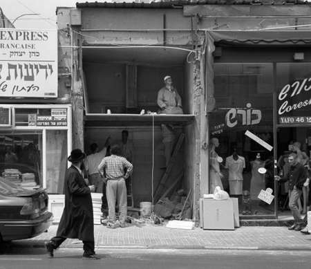 reconstruct: Jerusalem, Israel - Hasidic Jew pass by a praying muslim in a reconstruct store in Jaffa Road