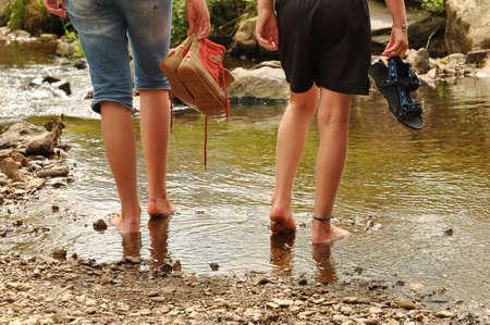 Twee tienermeisjes afkoelingsperiode hun voeten in een kreek in de Belgische Ardennen