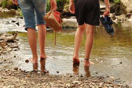 shoes off: Two teenage girls cooling off their feet in a creek in the Belgian Ardennes  Stock Photo