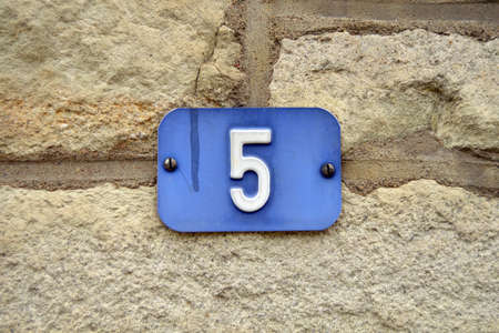 Number 5 - Blue House Number Five sign at a stone wall Zdjęcie Seryjne