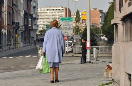 footway: Liege, Belgium - August 2011 - Woman walking her dog down the streets of Liege