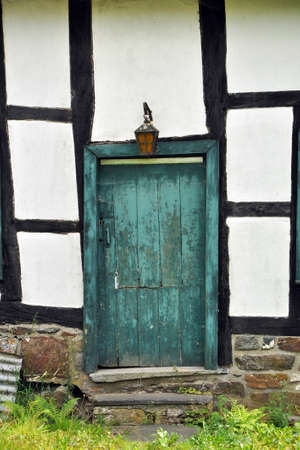 quaint:  Timber frame facade with a closed crooked old green wooden door Stock Photo
