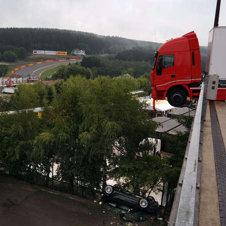 hangs: SPA-FRANCORCHAMPS, BELGIUM - JULY 28  A truck hangs off the Francorchamps circuit paddock as a car sits upside down after falling off the overhang on July 28, 2014 in Francorchamps, Belgium   Editorial