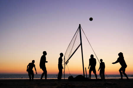 beach volleyball: Silhouettes of a group of young people playing beach volleyball on the beach in Brittany, France