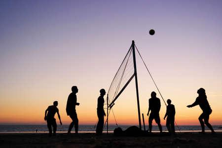 volleyball ball: Siluetas de un grupo de jóvenes jugando voleibol de playa en la playa en Bretaña, Francia