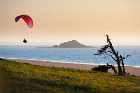 parapente: Parapente solitario durante la puesta de sol en el lado tierra, en Bretaña, Francia