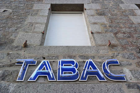 tobacco product: French Tabac Neon sign at facade of a tobacconist