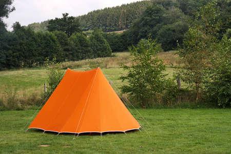 Camping in de Belgische Ardennen met een oranje doek tent op gras