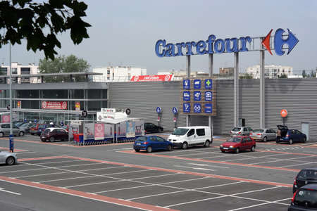 SAINT-LO, FRANCE - JULI 2014 - Facade and parking of a Carrefour hypermarket - Carrefour is a French multinational retailer, It is one of the largest hypermarket chains in the world Editorial