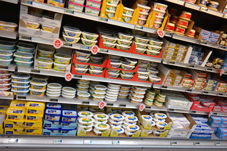 carrefour: NORMANDY, FRANCE - JULI 2014: Refrigerated shelves of butter and margarine at a Carrefour Hypermarket