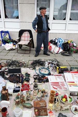 PETIT-Rechain, BELGIË - juli 2014 Verkoper met zijn waren op een Brocante, een rommelmarkt in België Stockfoto - 31111875