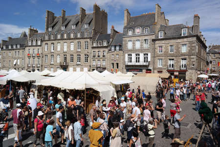 sword act: DINAN, FRANCE - JULY 2014:  Many of crowd people dressed up in a medieval costume on Fete des remparts, a hugely popular Knights Festival on July 20, 2014 in old city of Dinan, France