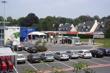 retailing: SAINT-LO, FRANCE - JULY 2014: Carrefour supermarkets in Europe have branched into petrol retailing, as shown by this filling station beside a hypermarket in Normandy, France