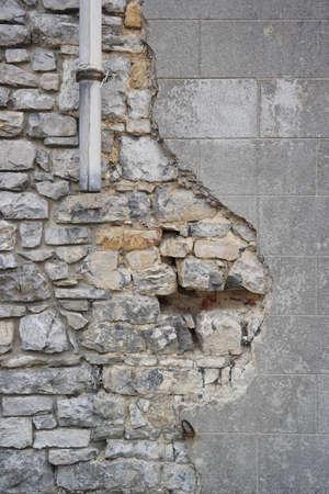 broken brick: Vintage brick wall texture with damaged plaster and broken drainpipe Stock Photo