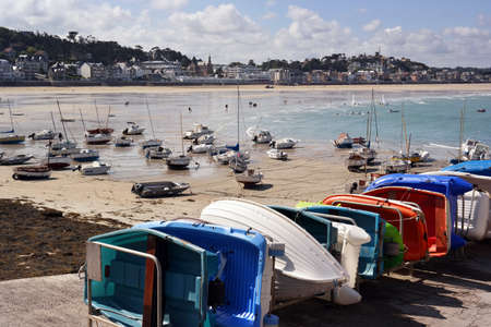 cotes d armor: Sailboats at ebb tide on the beach and small rowing boats at the quay of Pleneuf-Val-Andre harbour, Brittany, France Stock Photo
