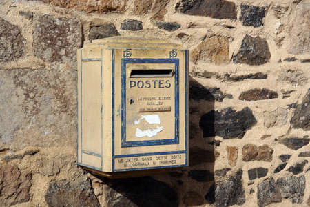 BRITTANY, FRANCE - JULY 2014: old yellow French postbox hanging on a wall in Brittany, France