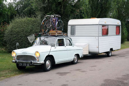 FRANCE - JULY 2014: Vintage car and caravan packed for holiday travel 新聞圖片