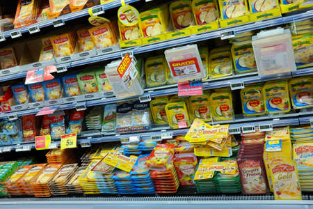 boycott: WALLONIA, BELGIUM - OCTOBER 2014: Refrigerated shelves with a variety of sliced cheese packages at a Carrefour Hypermarket Editorial
