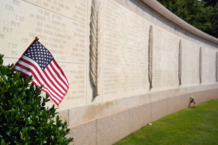 allies: An American flag in front of Walls of the Missing at The Normandy American Cemetery in Colleville-sur-Mer, France Editorial