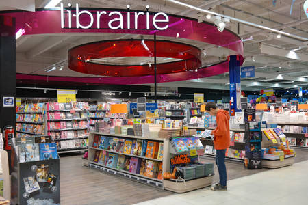 BELGIUM - OCTOBER 2014:  Boy is reading a comic book at the librairie section in a Carrefour hypermarket in Belgium Publikacyjne