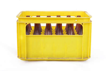 Dusty vintage yellow beer crate with empty bottles