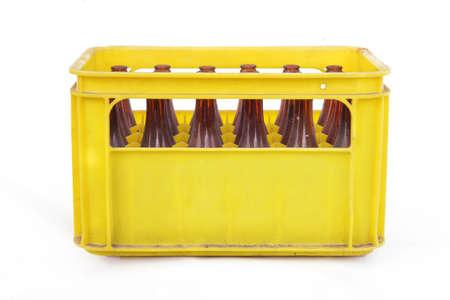 Stoffige vintage gele bier krat met lege flessen Stockfoto