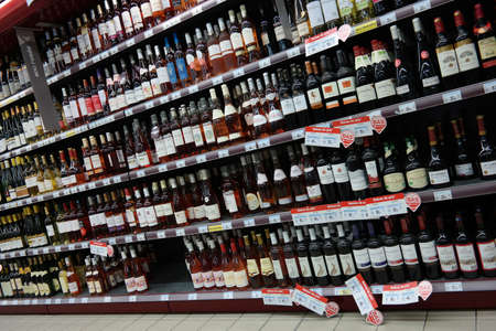 wine trade: FRANCE - JULY 2014: The wine section of a Carrefour supermarket in Normandy, France - France is one of the largest wine producers in the world Editorial