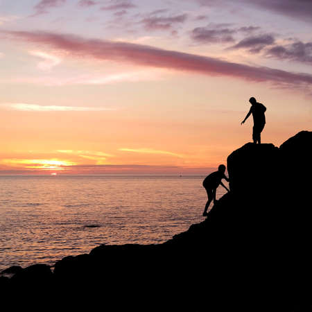 Climbing silhouette at rocky seashore gets a helping hand to get up during sunset in Brittany, France photo