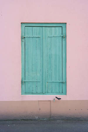 Pastel Window with green shutters closed, set in a pink plastered wall in Saint-Malo, France photo