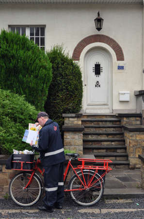 post mail: SPA, BELGIUM - AUGUST 2010: Belgian Postman, employee or bpost, also known as the Belgian Post Group, the Belgian company responsible for the delivery of national and international mail. Editorial