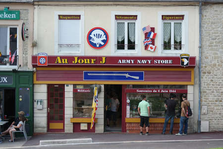 munition: NORMANDY, FRANCE - JULY 2014: Tourists looks into the window of a souvenir shop for the landings of D-day in Sainte Mere Eglise