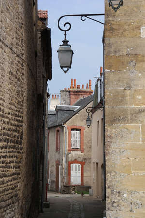 unruffled: Street view into a characteristic bystreet with lanterns in Carentan, Normandy, France