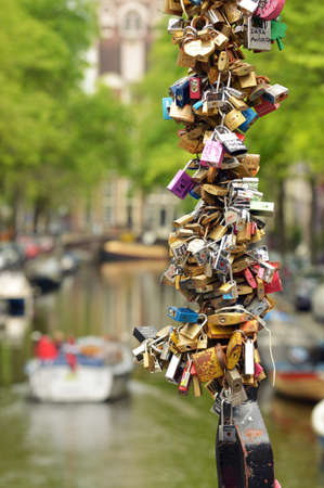 pad lock: AMSTERDAM, NETHERLANDS - APRIL 2014: Padlocks closed on a bridge as an eternal love symbol in front of an Amsterdam canal with boats Editorial