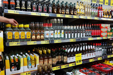 UELSEN, GERMANY - SEPTEMBER 2014:  A hand takes a bottle from aisle filled with spirits in a Lidl supermarket
