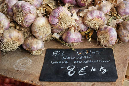 ail: Bulbs of Garlic priced on a blackboard at a market in Brittany, France