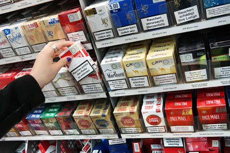 MEPPEN, GERMANY - FEBRUARY 2015: Cigarette packages with the warning: smoking is lethal, in a Kaufland supermarket cigarette counter in Meppen, Germany Publikacyjne