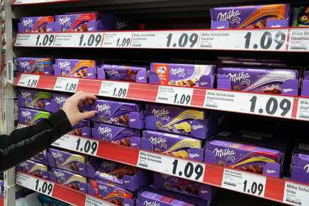 mount price: MEPPEN, GERMANY - FEBRUARY 2015: Shelves with a variety of Milka chocolate bars in a Kaufland supermarket. Milka is a traditional Swiss brand of chocolate confection