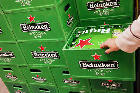 pilsener: THE NETHERLANDS - MARCH 2015: Stack of Heineken beer crates in a wholesale.  Heineken ranks as the third largest brewer in the world