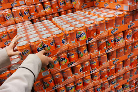 six pack: THE NETHERLANDS - MARCH 2015: Stack of with 24-packs of shrink wrapped Fanta cans in a wholesale.  Fanta is a global brand of fruit-flavored carbonated soft drinks created by The Coca-Cola Company.