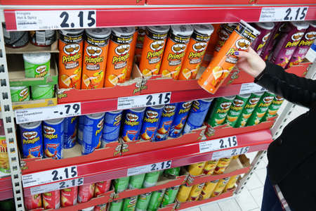 stackable: GERMANY - FEBRUARY 2015: Shelves with a variety of Pringles Chips in a Kaufland supermarket. Pringles is a brand of potato and wheat-based stackable snack chips owned by the Kellogg Company