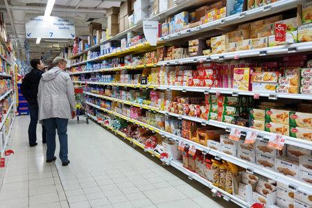 VALONIA, BÉLGICA - OCTUBRE 2014: El hacer compras en la sección de galletas en un hipermercado Carrefour Editorial