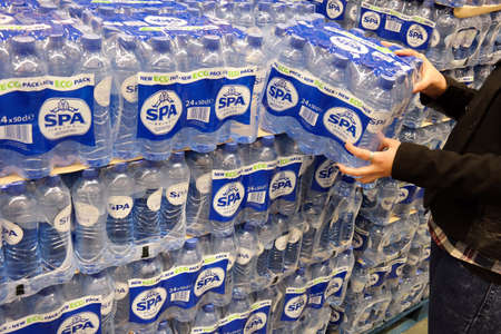 six packs: THE NETHERLANDS - MARCH 2015: Stack of with 24-packs of shrink wrapped Spa Reine water bottles in a wholesale.  Spa is a brand of mineral water from Spa, Belgium Editorial