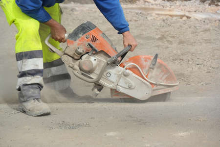 construction industry: Construction worker operated Circular saw with a diamond blade for cutting asphalt and concrete. Stock Photo