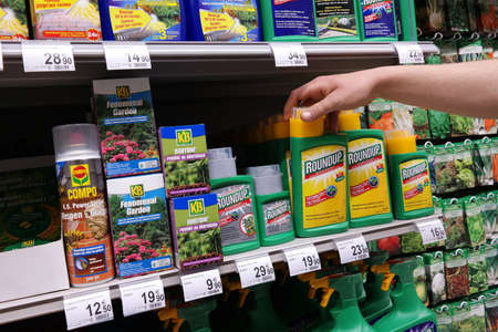MALMEDY BELGIUM MAY 2015: Shelves with a variety of Herbicides in a Carrefour Hypermarket. Roundup is a brand name of an herbicide made by Monsanto.