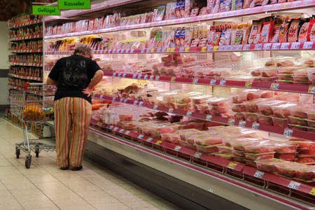 refrigerated: GERMANY - MAY 2015: Customer selecting packaged meat in refrigerated section of a Kaufland hypermarket