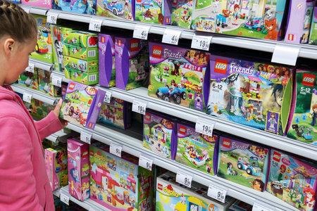 juguete: Malmedy, Bélgica - 27 de julio: La muchacha en la sección de selección de juguetes Lego de un hipermercado Carrefour. Lego es una popular línea de juguetes de construcción fabricados por el Grupo de Lego