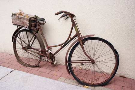 Vintage ladies bike. An old weathered rusty bicycle with basket parked against a wall