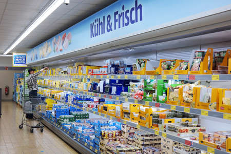 MONSCHAU, GERMANY - JULY 2015: Man with a shopping trolley in the refrigerated fresh products aisle of an Aldi supermarket. Aldi is a global discount supermarket chain. Publikacyjne